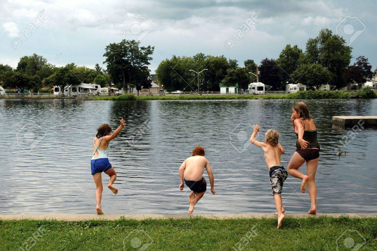Kids Swimming In A Lake four kids enjoying an afternoon dip in lake stock photo, picture