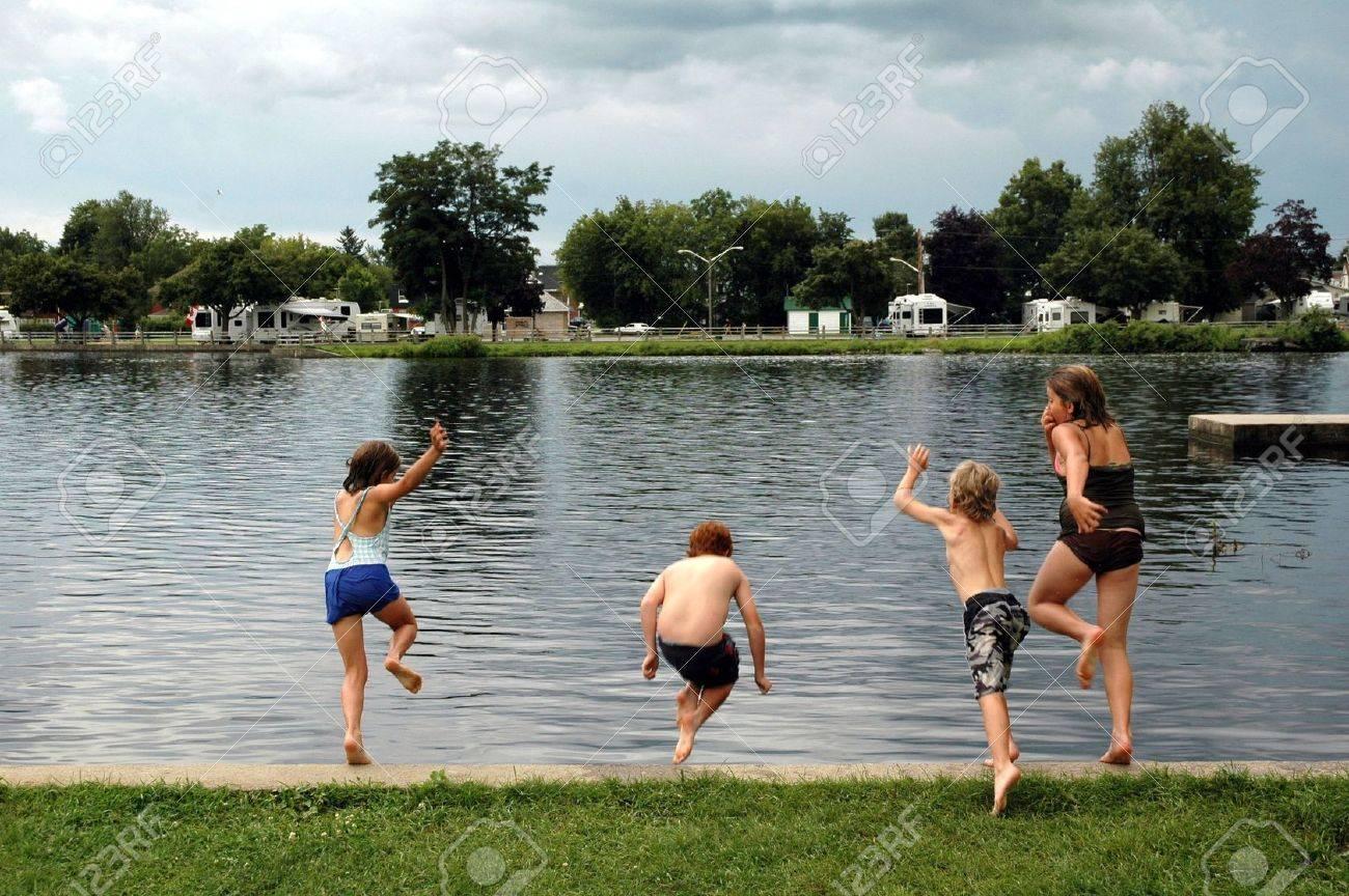 Kids Swimming In A Lake four kids enjoying an afternoon dip in lake stock photo, picture