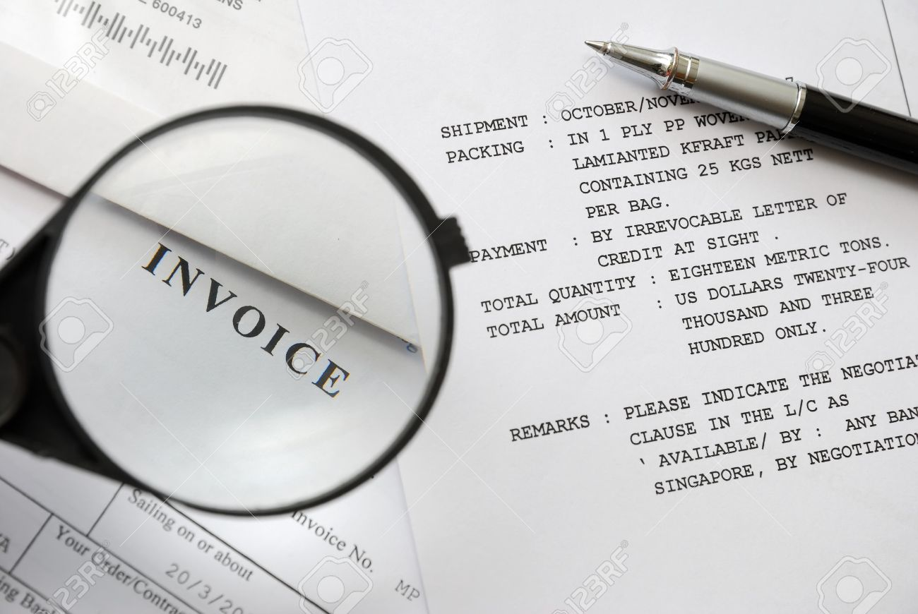Magnifying Glass On Invoice Text With Pen On Purchase And Sales Related  Documents In Background.