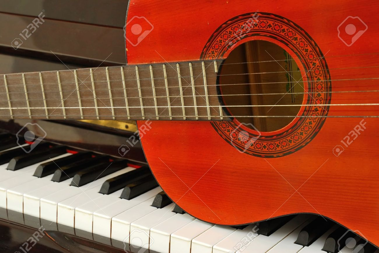 Acoustic guitar on piano keyboard. For concepts like music composition and creativity. Stock Photo - 7114791