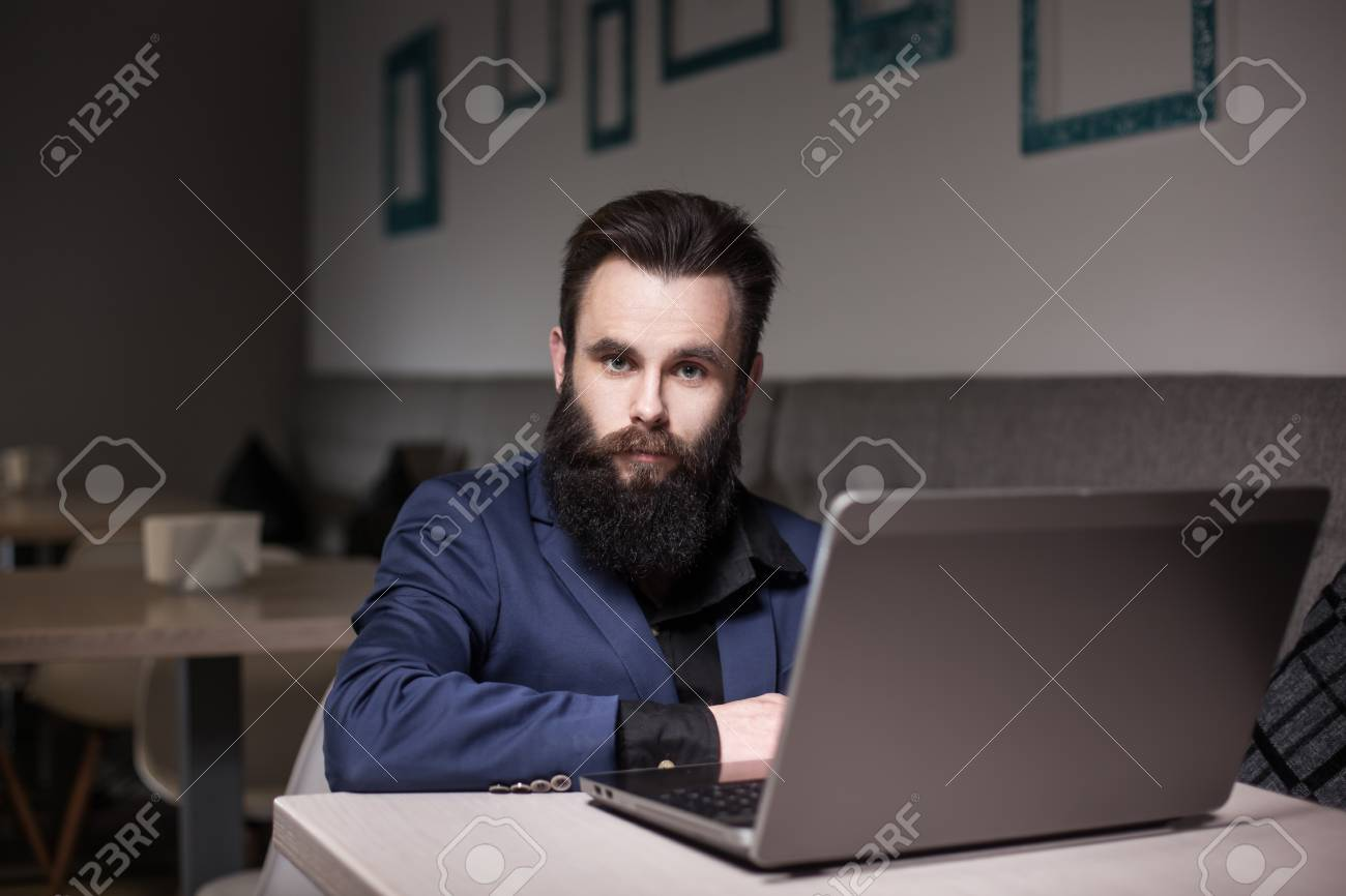 af815030c5 Banque d'images - Homme barbu en costume et avec ordinateur portable assis  dans un café et surfer sur Internet;
