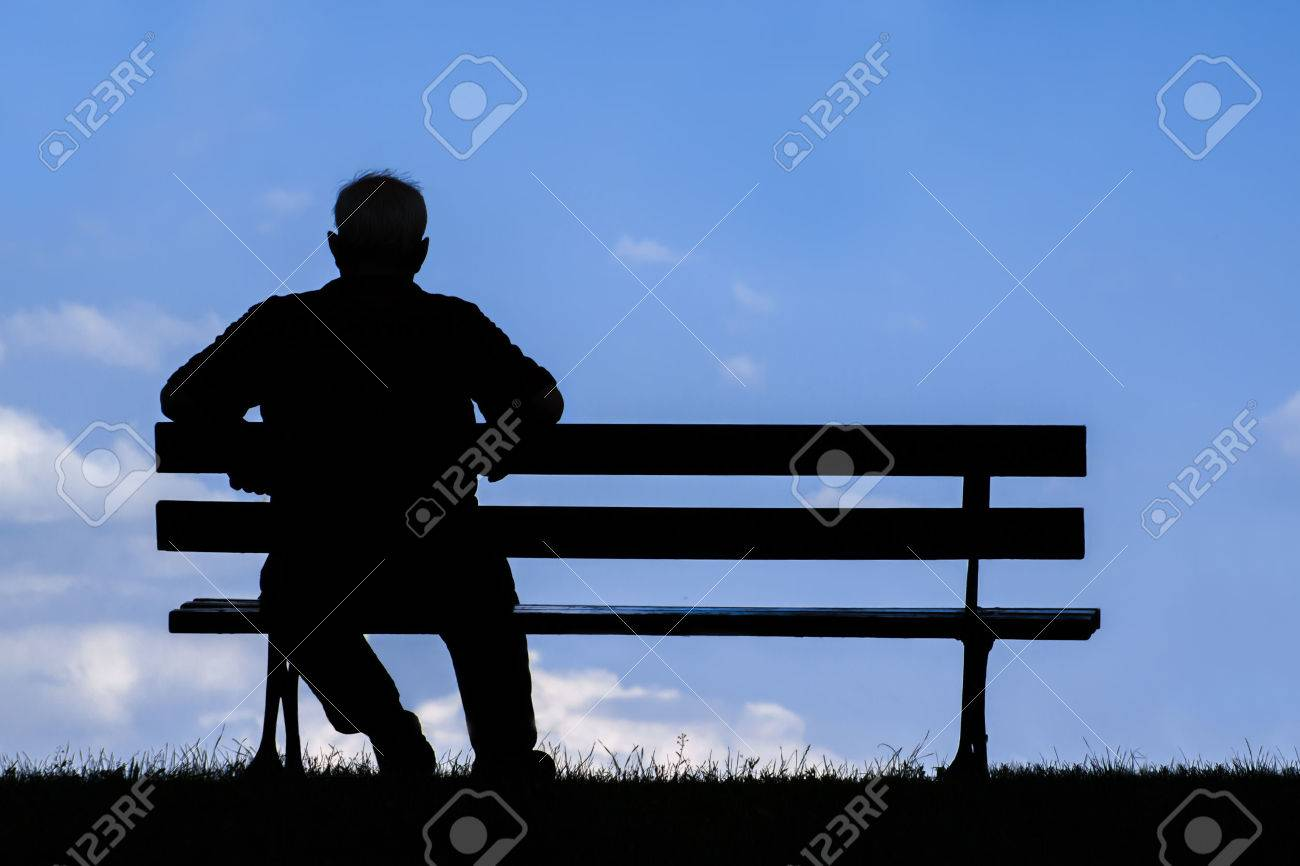 old man sitting alone on park bench; silhouette of resting retired senior - 56077829
