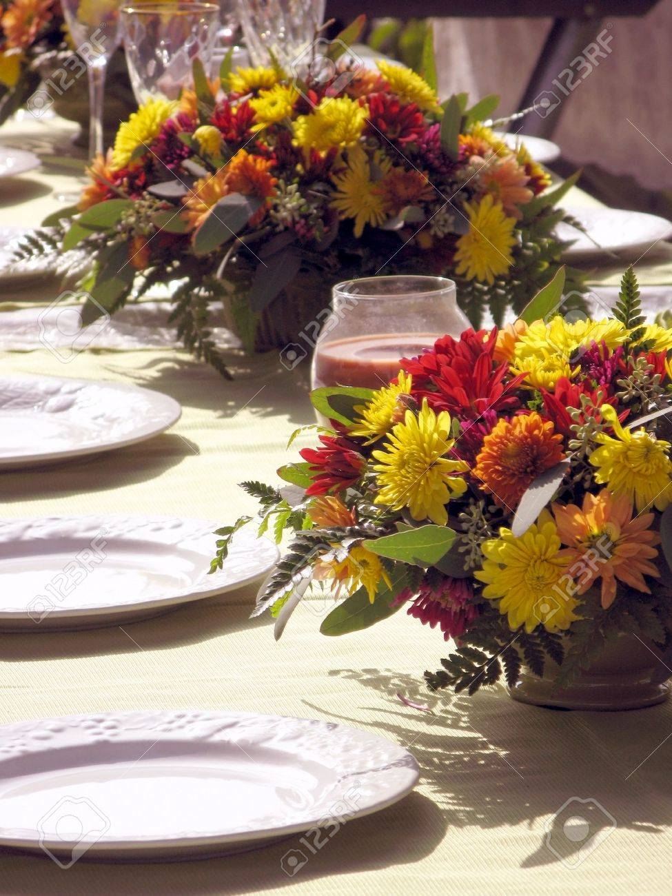 outdoor table setting with flowers in fall colors red yellow golds and orange with white plates & Outdoor Table Setting With Flowers In Fall Colors Red Yellow.. Stock ...