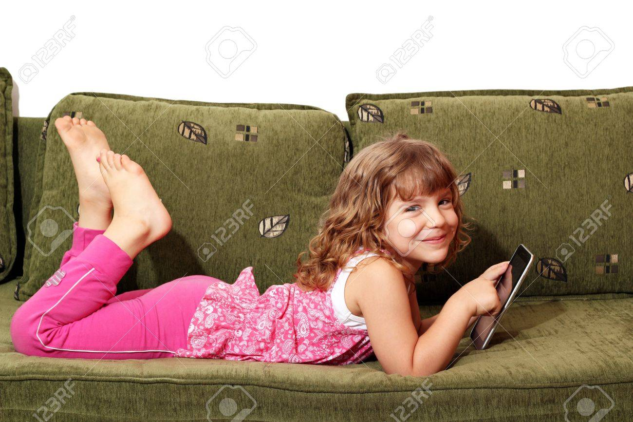 happy little girl lying on bed with tablet Stock Photo - 14604591