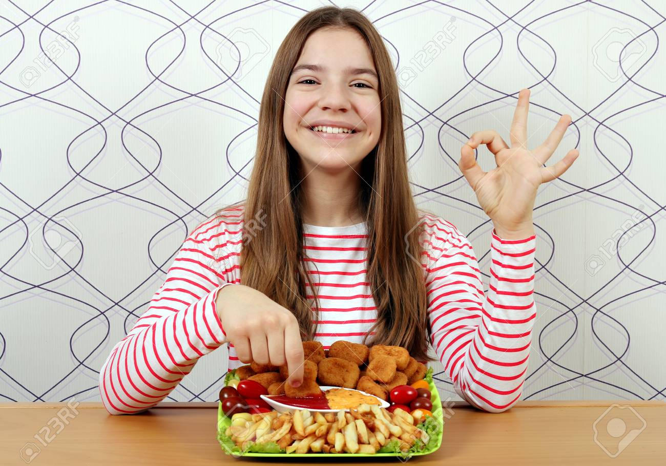 Happy teenage girl with tasty chicken nuggets and ok hand sign - 125471835