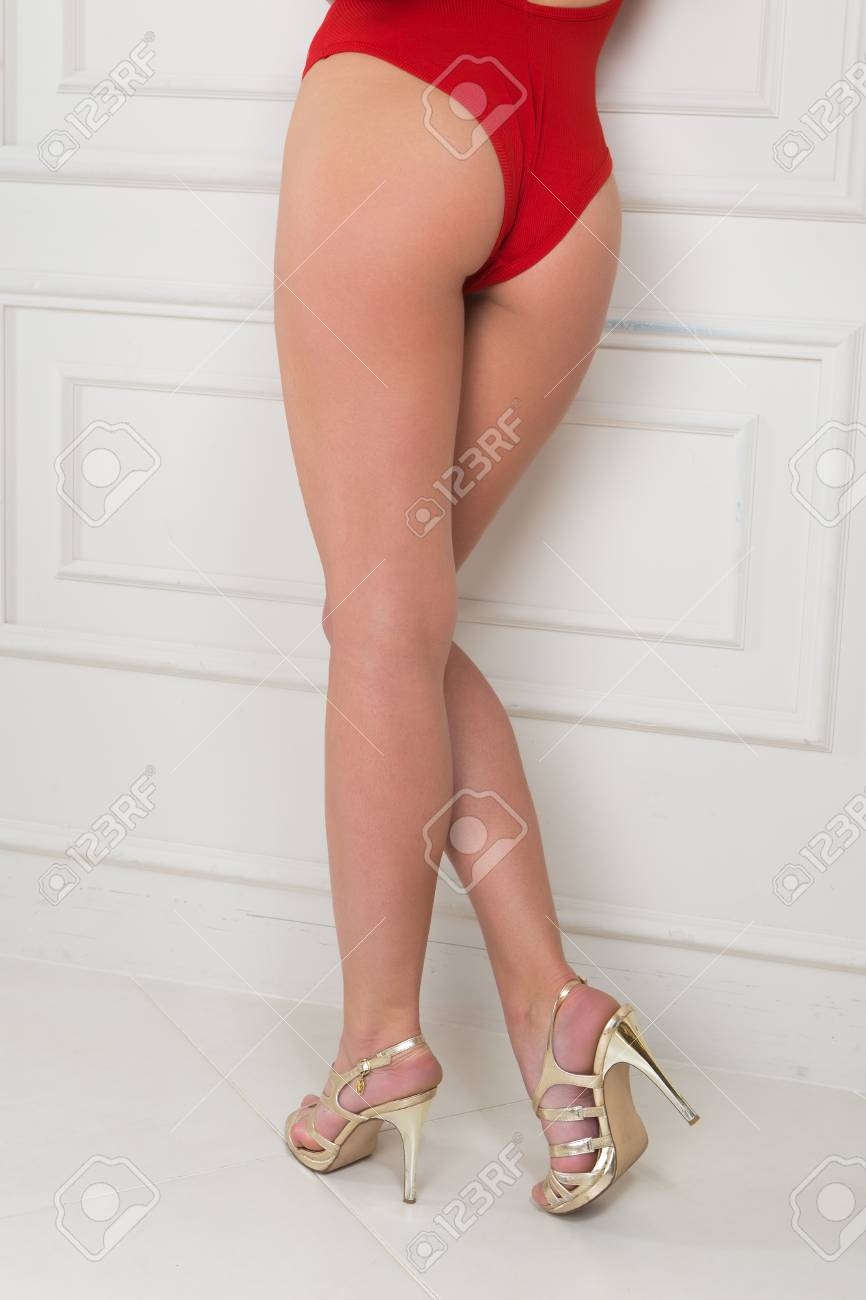 A girl in a red swimsuit demonstrates the ass and legs near the wall Stock  Photo
