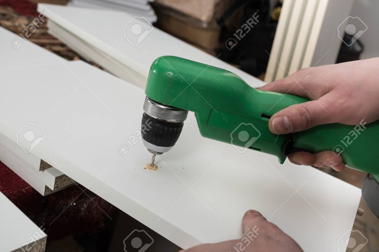 Carpenter Drills A Hole In The Component Parts Of A White Kitchen ...