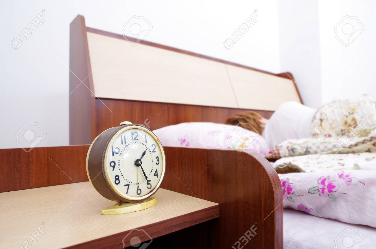woman and alarm clock in the bedroom