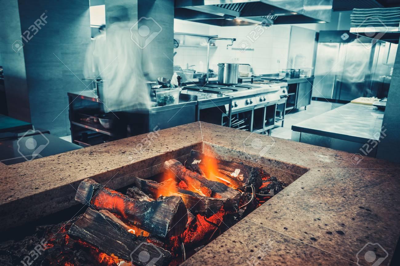 intérieur de la cuisine du restaurant: brasero à bois brûlant, en