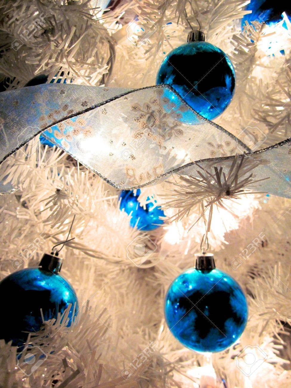 White christmas tree decorations blue - Blue Christmas Ornaments Hanging On A Lit White Christmas Tree Stock Photo 8592037