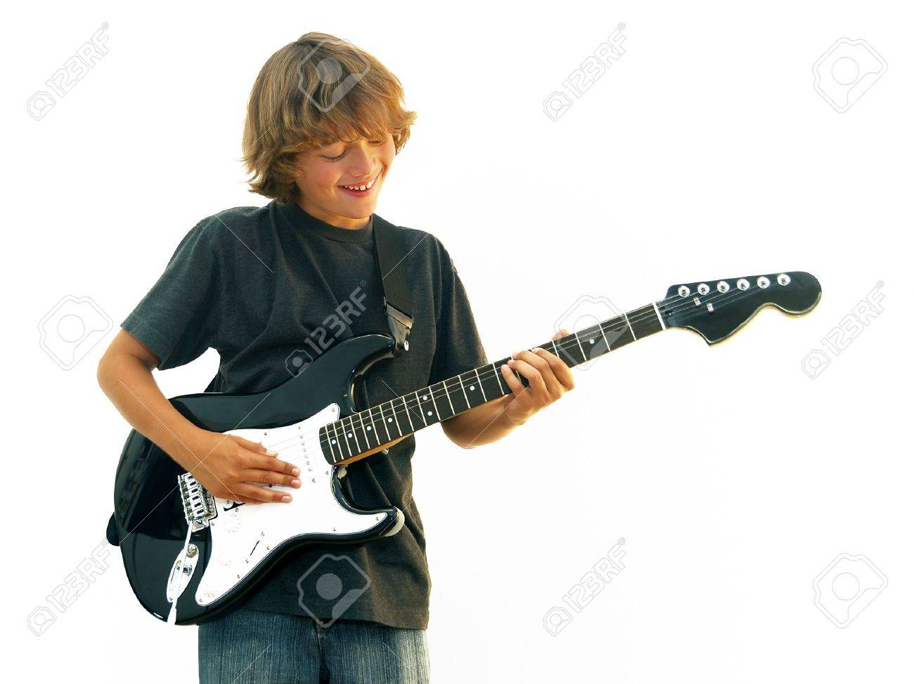 Smiling teen boy playing electric guitar isolated over white. Stock Photo - 4754581