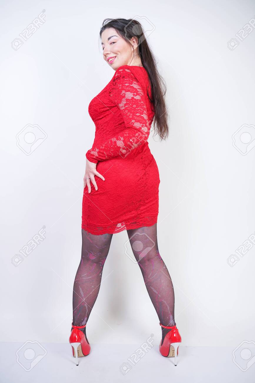Portrait of happy and confident plus size model in red dress - 128050899