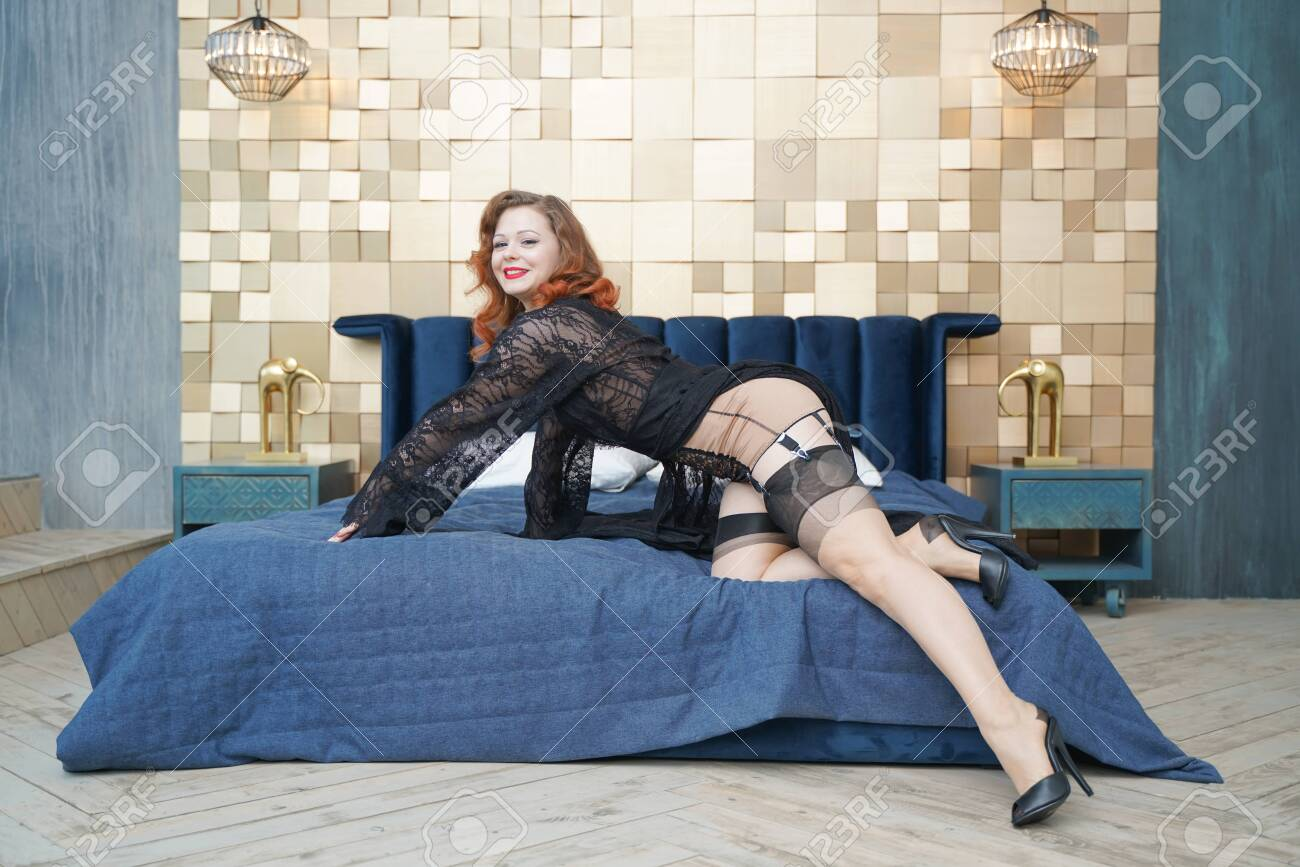 Young woman with black retro lingerie and nylon vintage stockings on bed - 128549672
