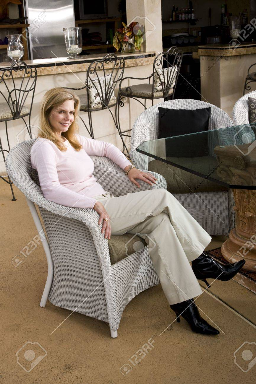Portrait Of Smiling Mature Woman Sitting In White Wicker Chair Stock Photo Picture And Royalty Free Image Image 6329023