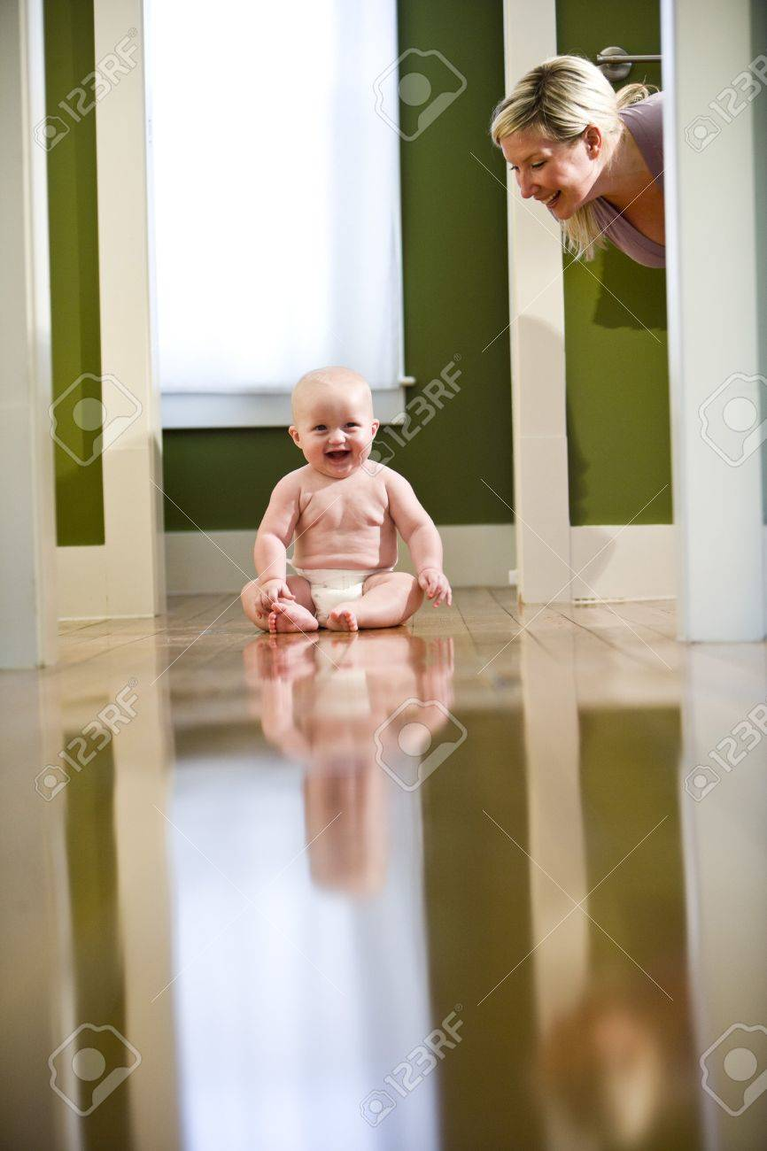 Cute seven month old chubby baby wearing diaper sitting on floor laughing at mother Stock Photo - 6610596