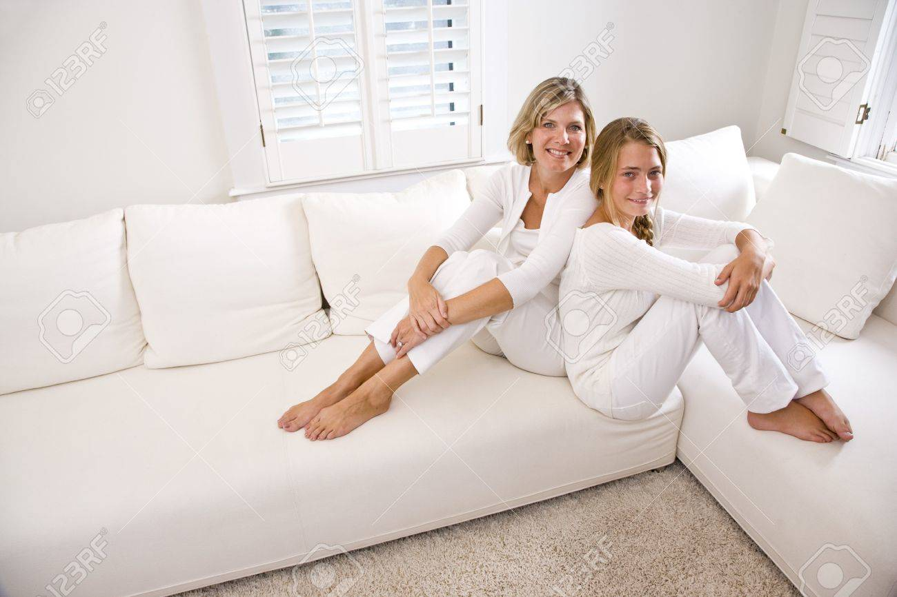 Mother and teenage daughter relaxing at home in white living room Stock Photo - 6610696