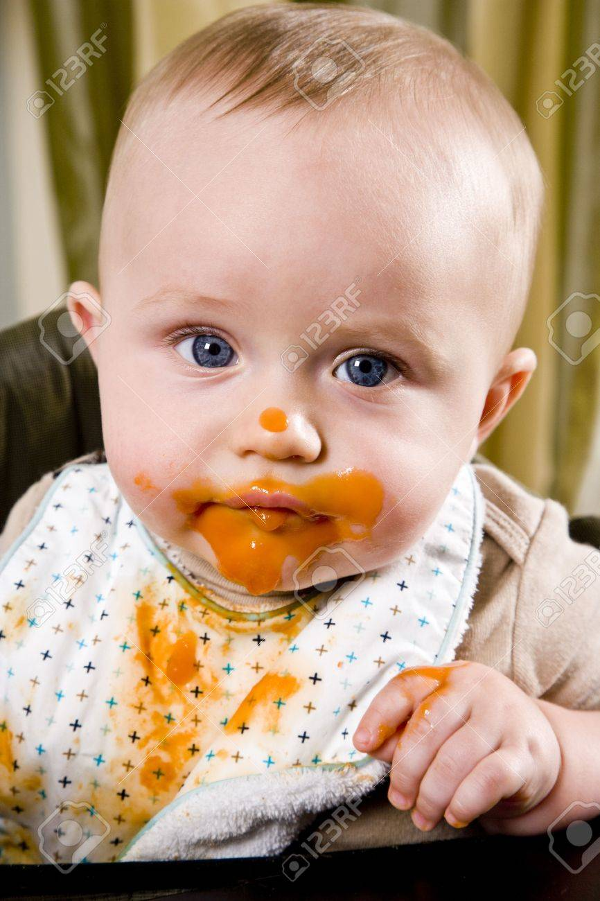 Messy six month old baby wearing bib after eating solid food Stock Photo - 6644341