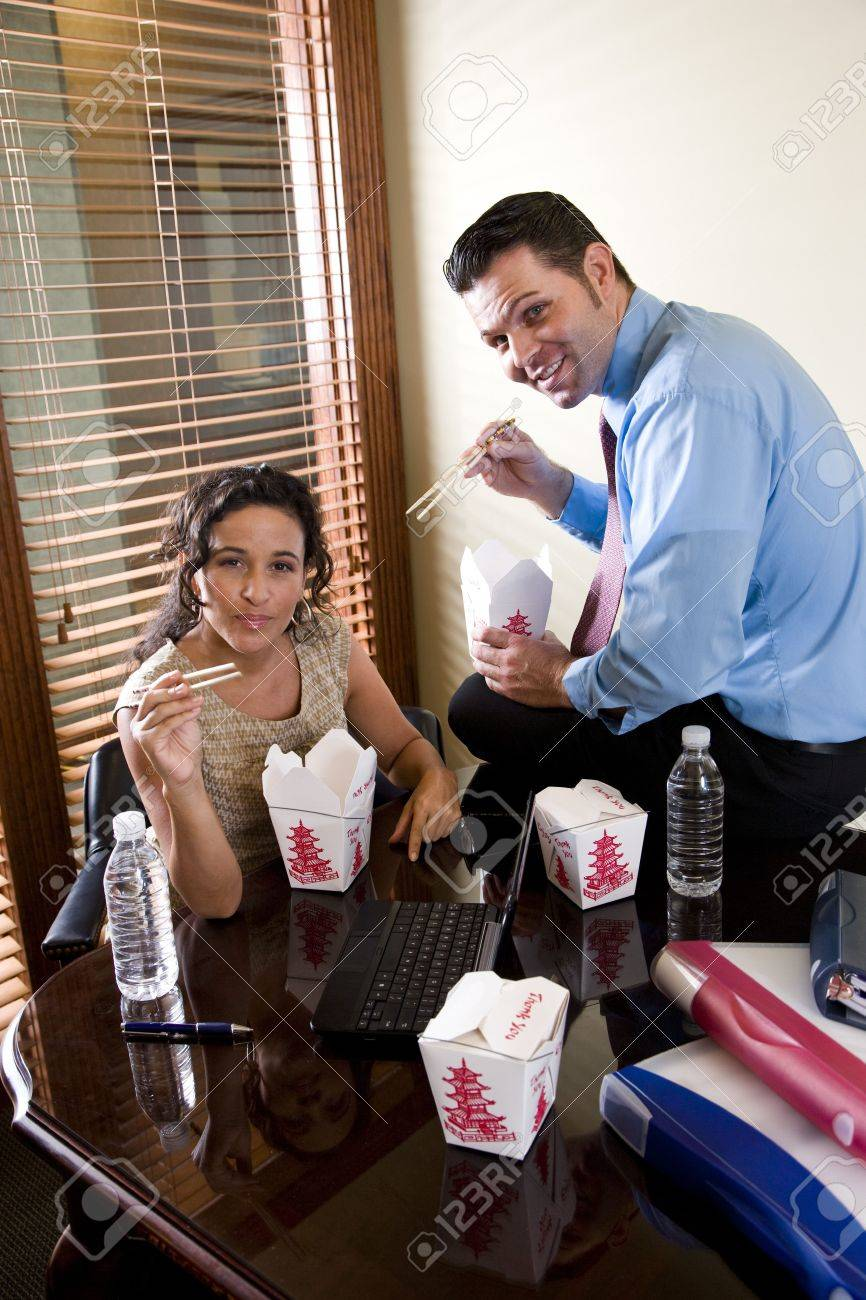 Office workers eating Chinese take-out food in boardroom while working on laptop Stock Photo - 6683617