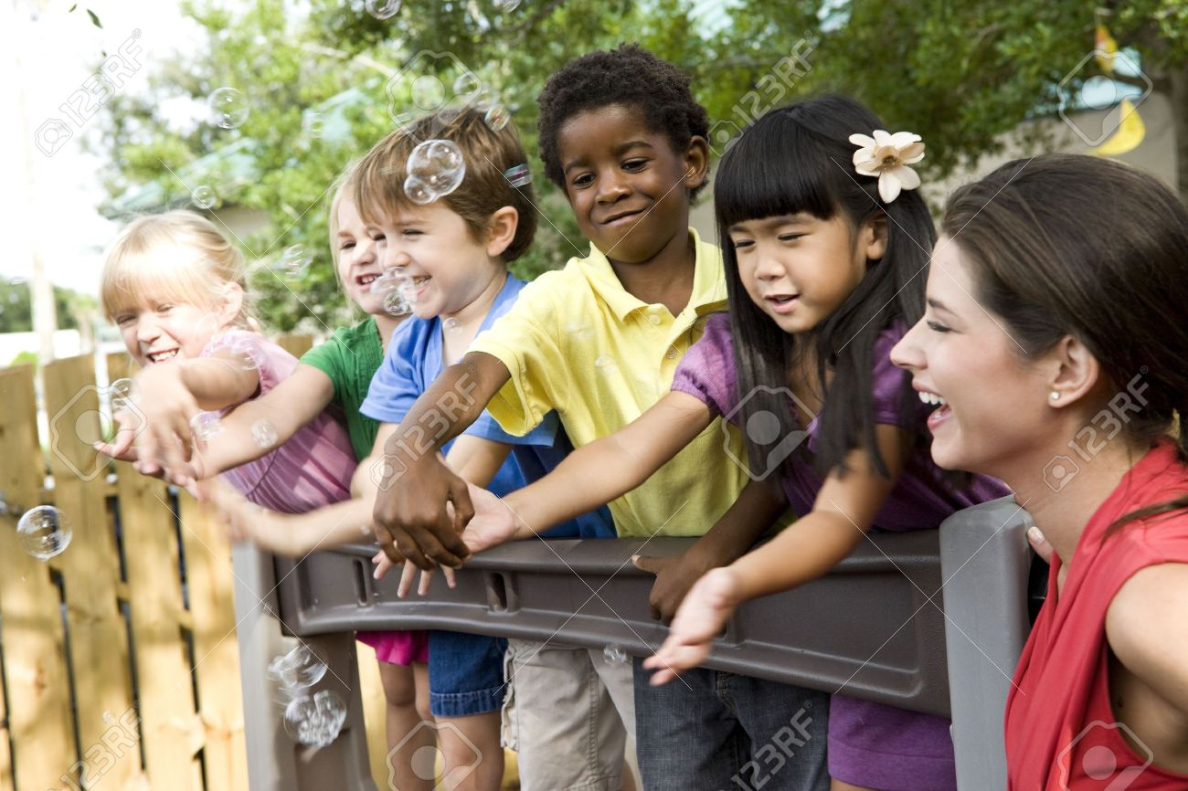 Diverse group of preschool 5 year old children playing in daycare with teacher Stock Photo - 6683630