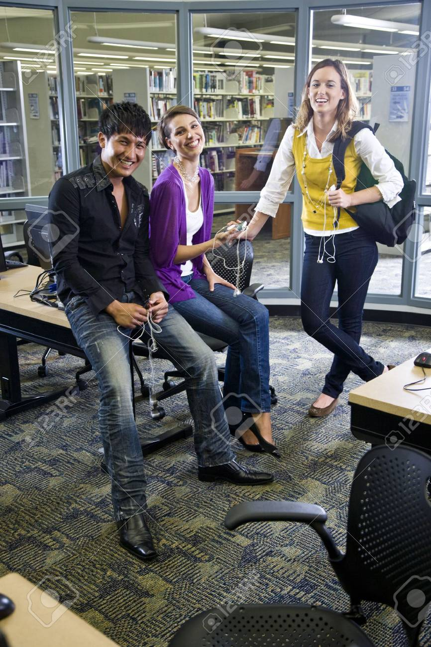 Three university students looking at music players in school library Stock Photo - 6799520