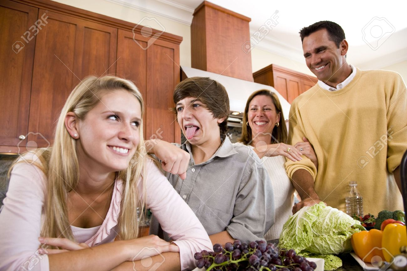 Happy family in kitchen - Happy Family With Two Teenage Children Making Funny Faces In Kitchen Stock Photo 6865135