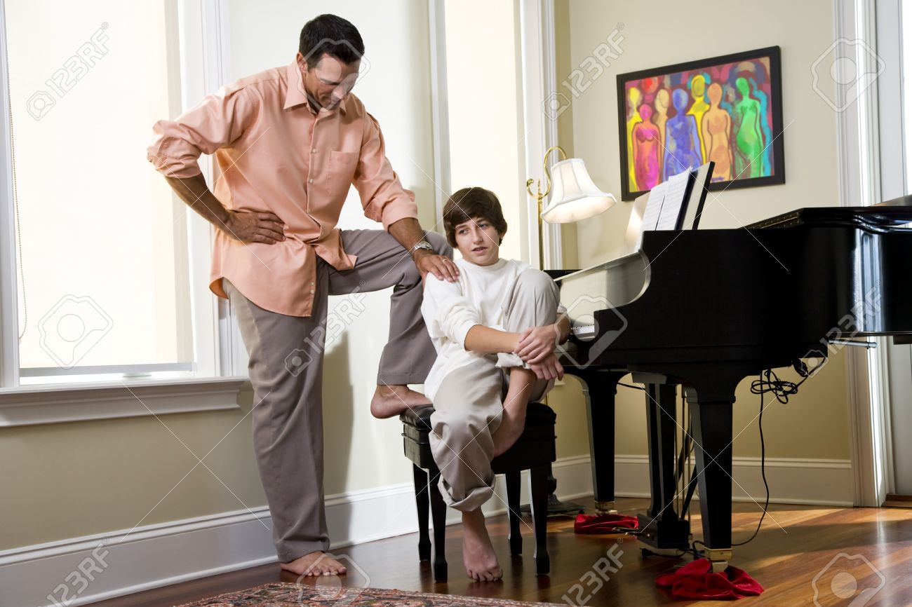 Serious father talking to teenage son at home by piano Stock Photo - 6865099