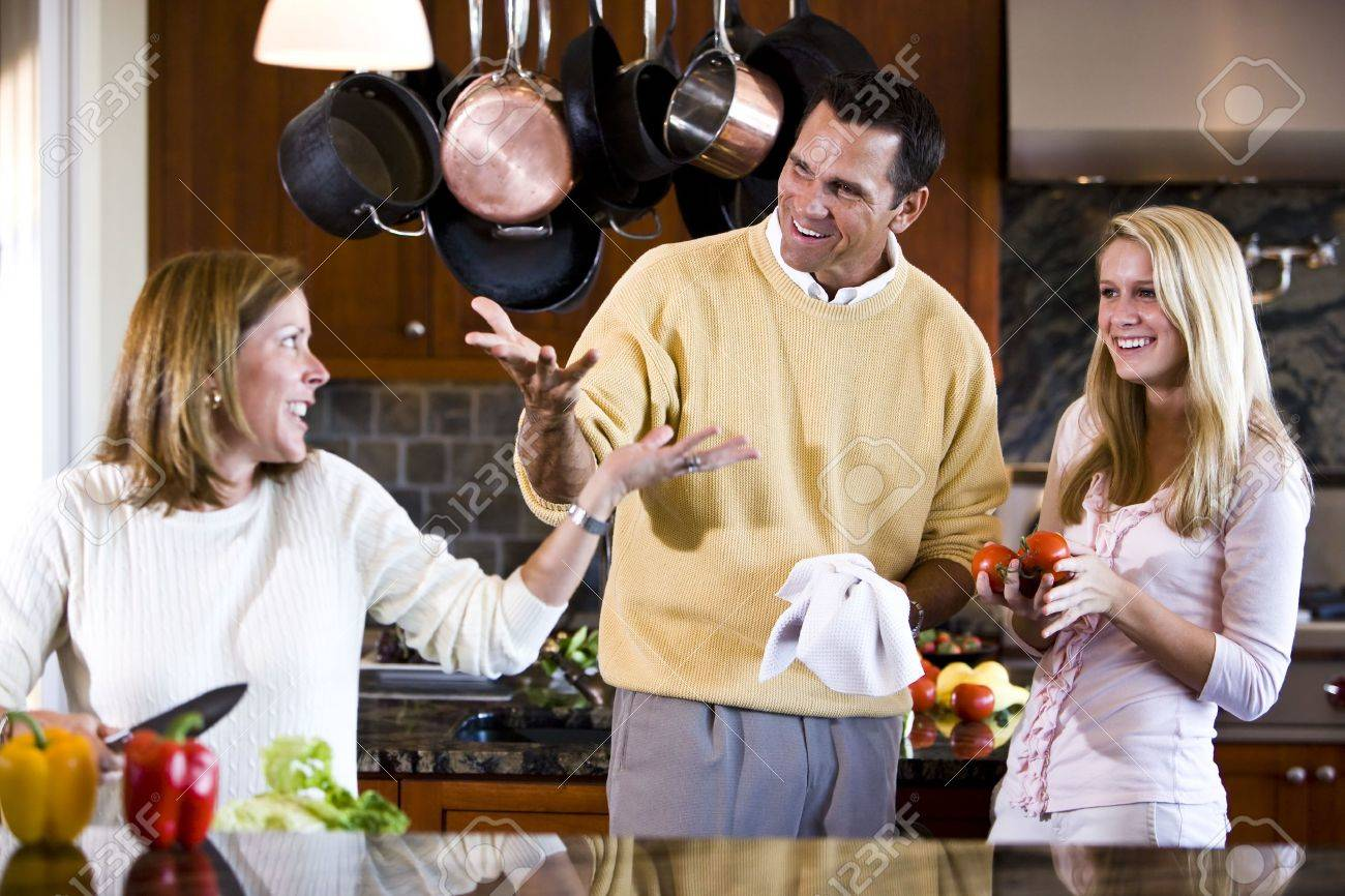 Family with teen girl talking together in kitchen