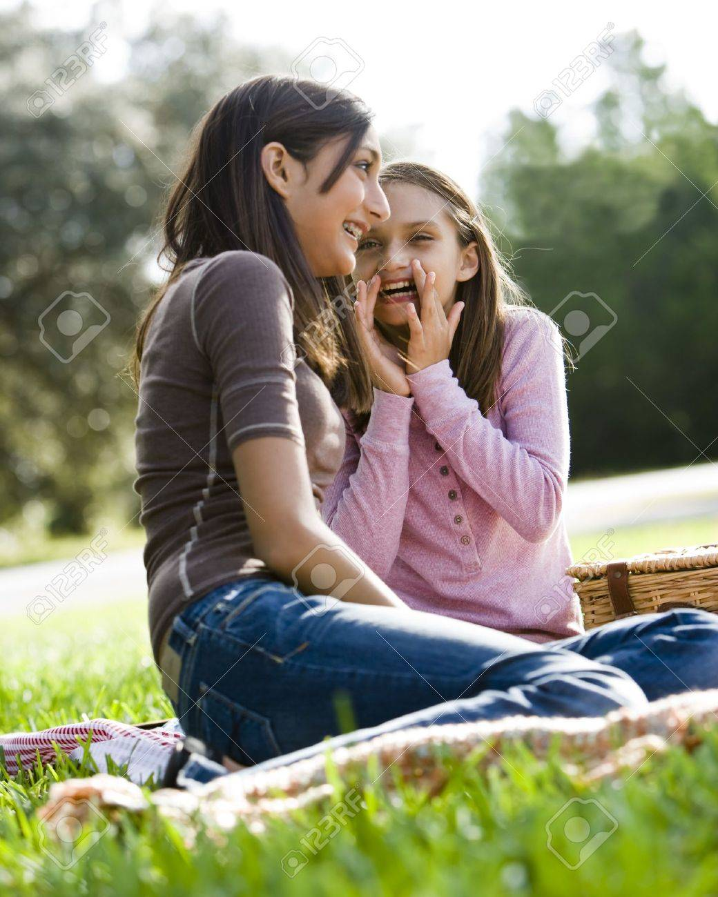 Girls whispering to each other at picnic in park Stock Photo - 6865208