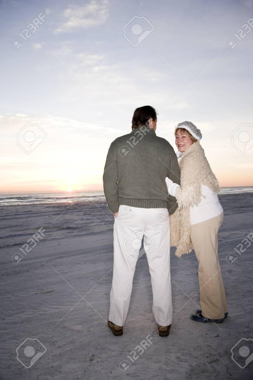 Affectionate senior couple in sweaters on beach at dawn Stock Photo - 7018706