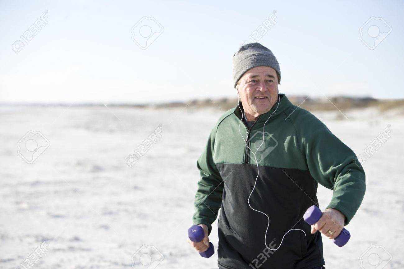 Mature man exercising with hand weights on beach staying fit Stock Photo - 7018691