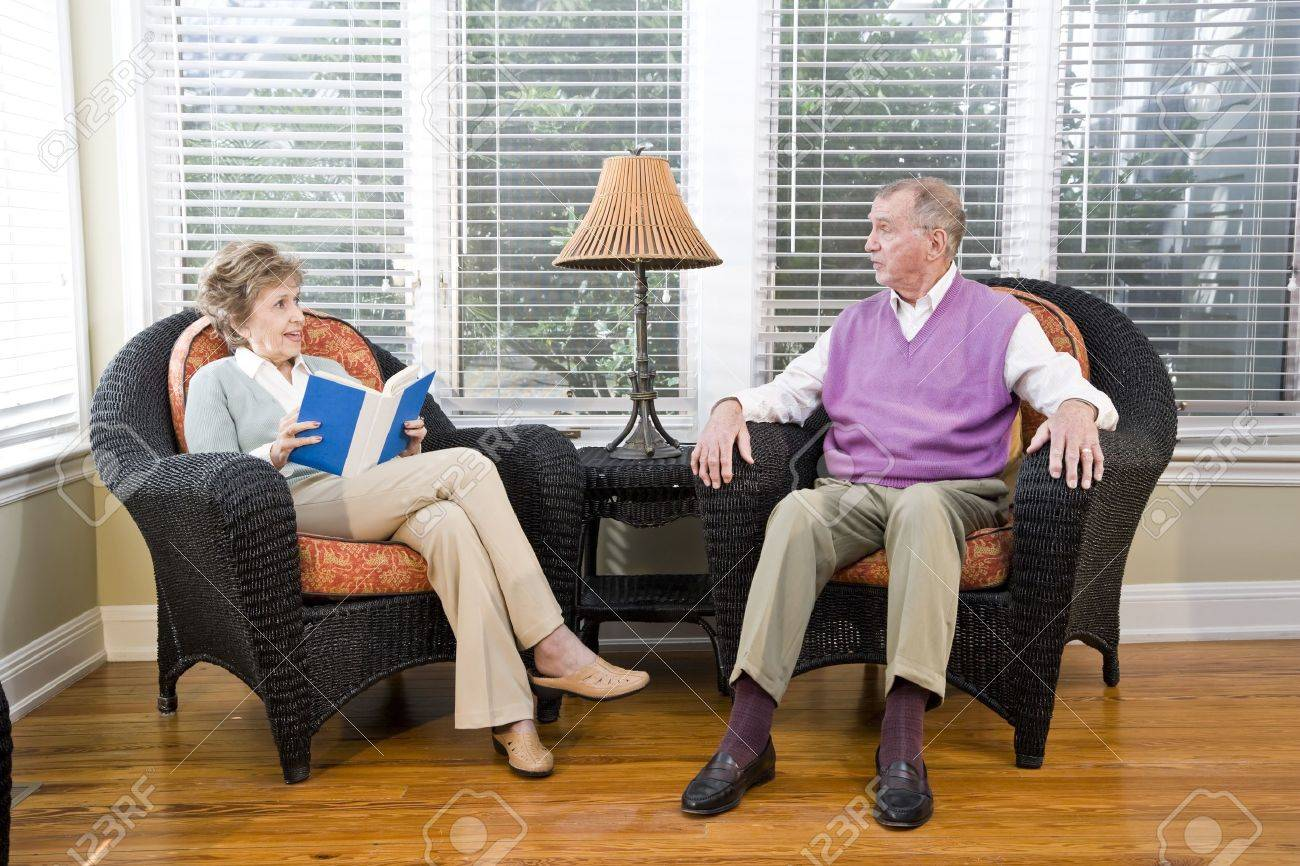 Senior couple sitting on living room chair reading and chatting Stock Photo  - 7181889 - Senior Couple Sitting On Living Room Chair Reading And Chatting