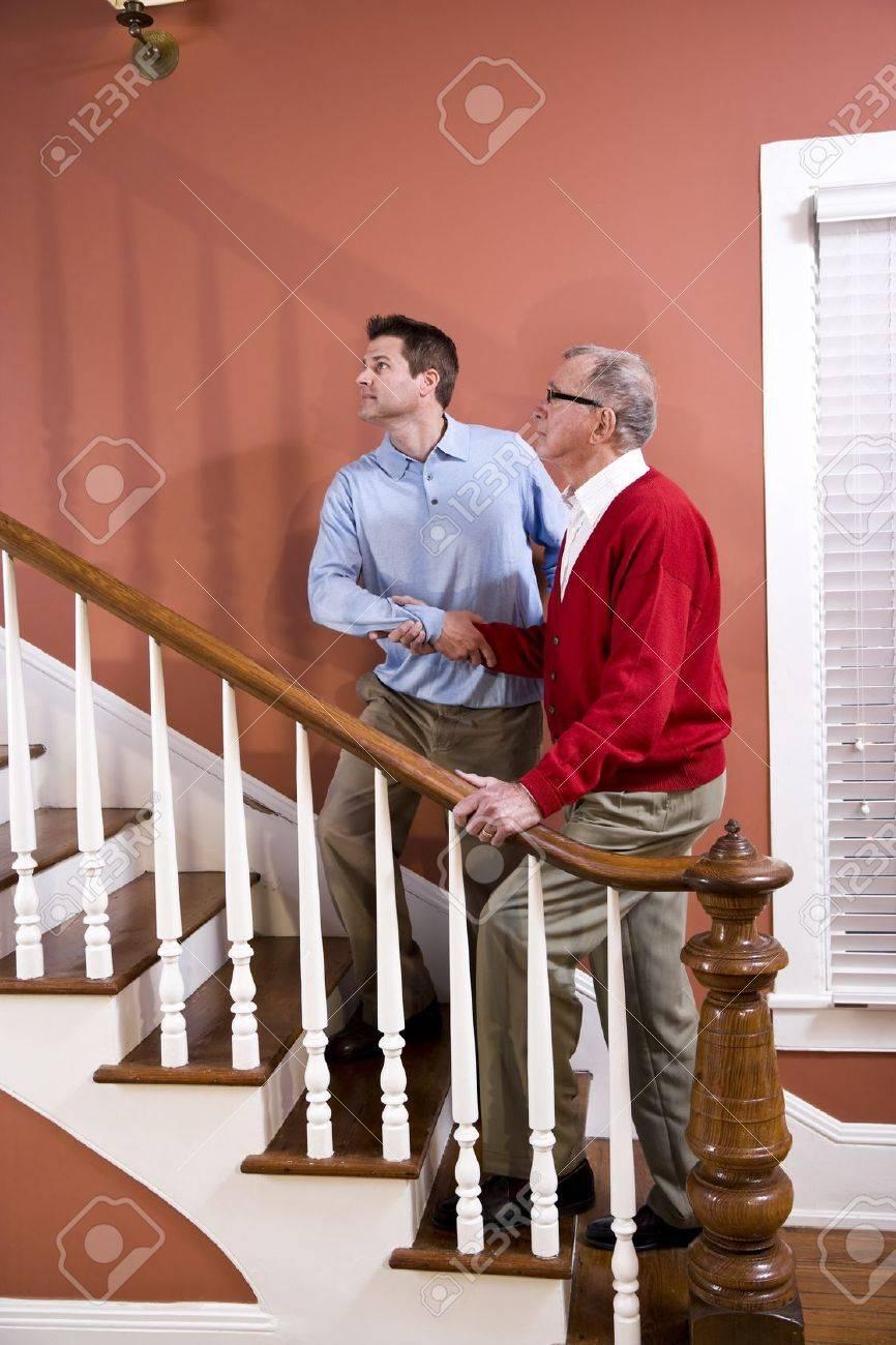 Homme aider le père supérieur montée escalier à la maison
