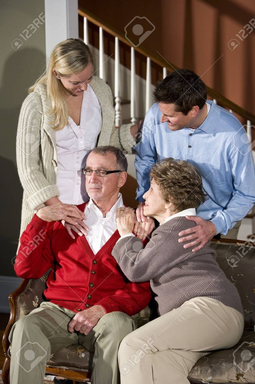 Senior couple on couch at home with adult children Stock Photo - 7181895