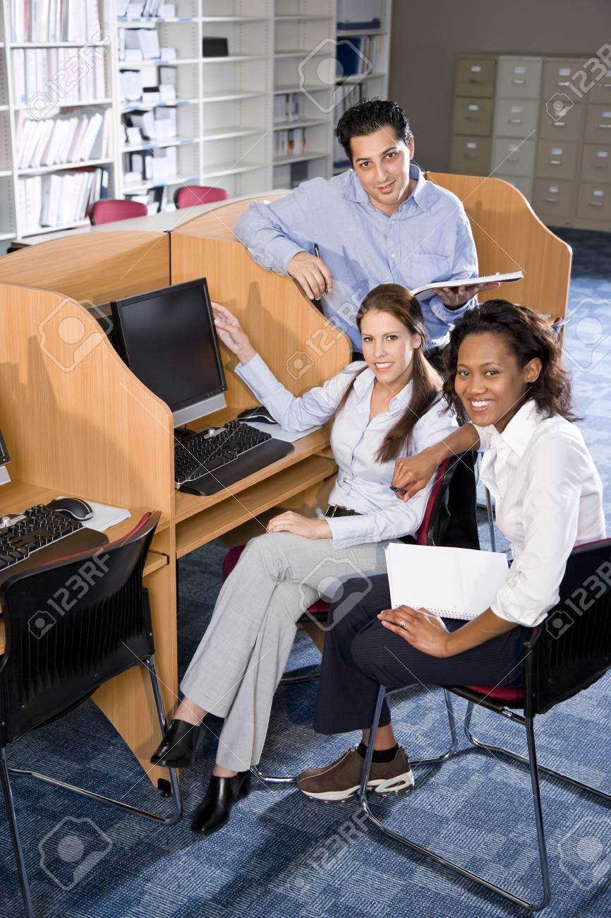 Diverse university students at library computer studying Stock Photo - 7159246