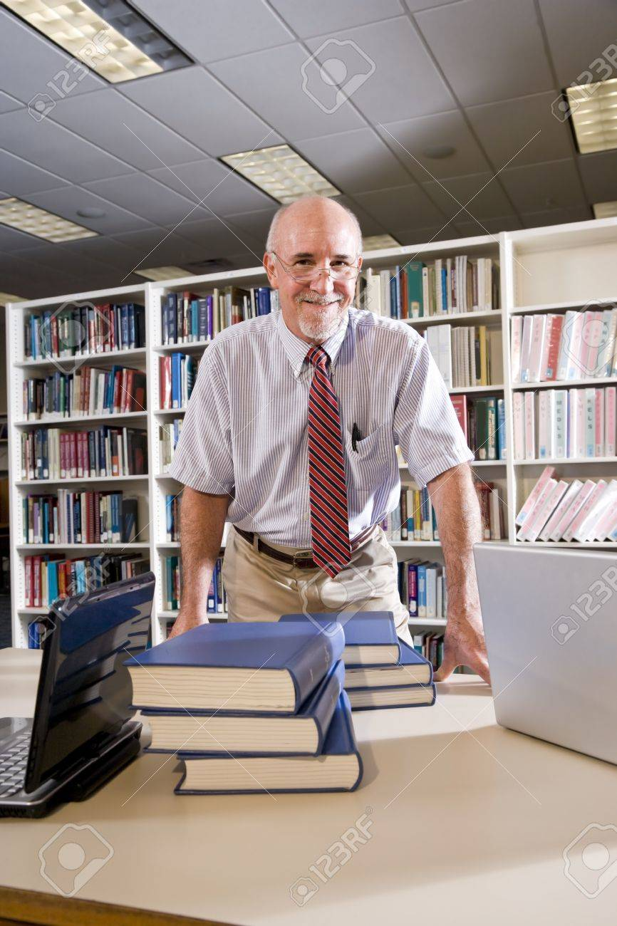 portrait of mature man at library table textbooks professor portrait of mature man at library table textbooks professor researching stock photo 7159229