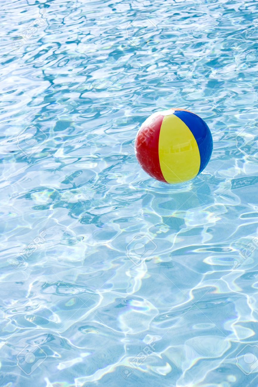 Pool Water With Beach Ball beach ball floating on surface of swimming pool water stock photo