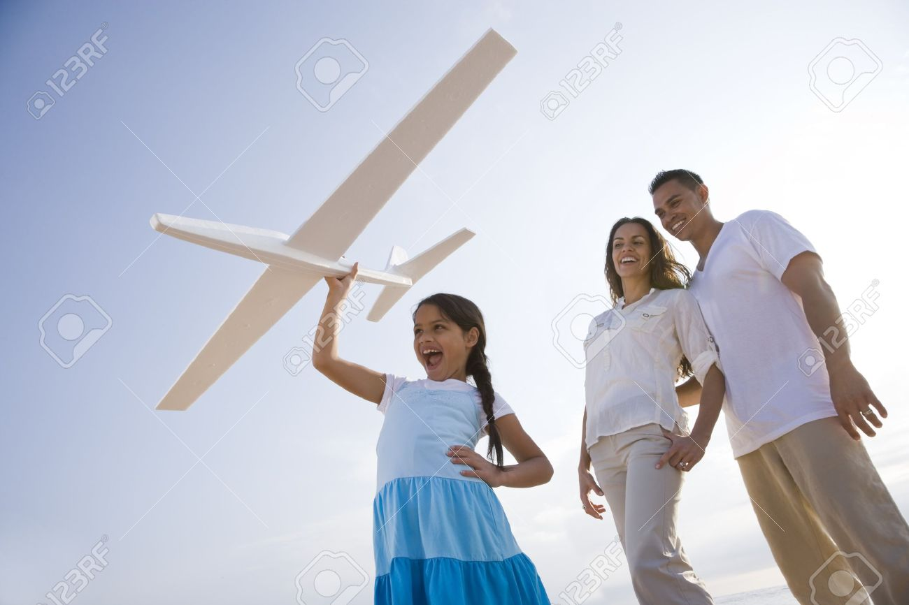 Hispanic family and 9 year old daughter having fun with toy plane Stock Photo - 7219839