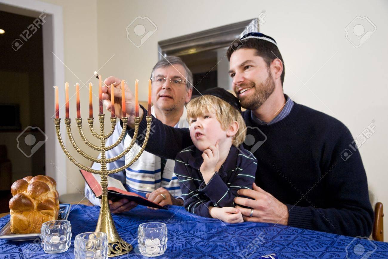Three generation Jewish family lighting Chanukah menorah Stock Photo - 7635059