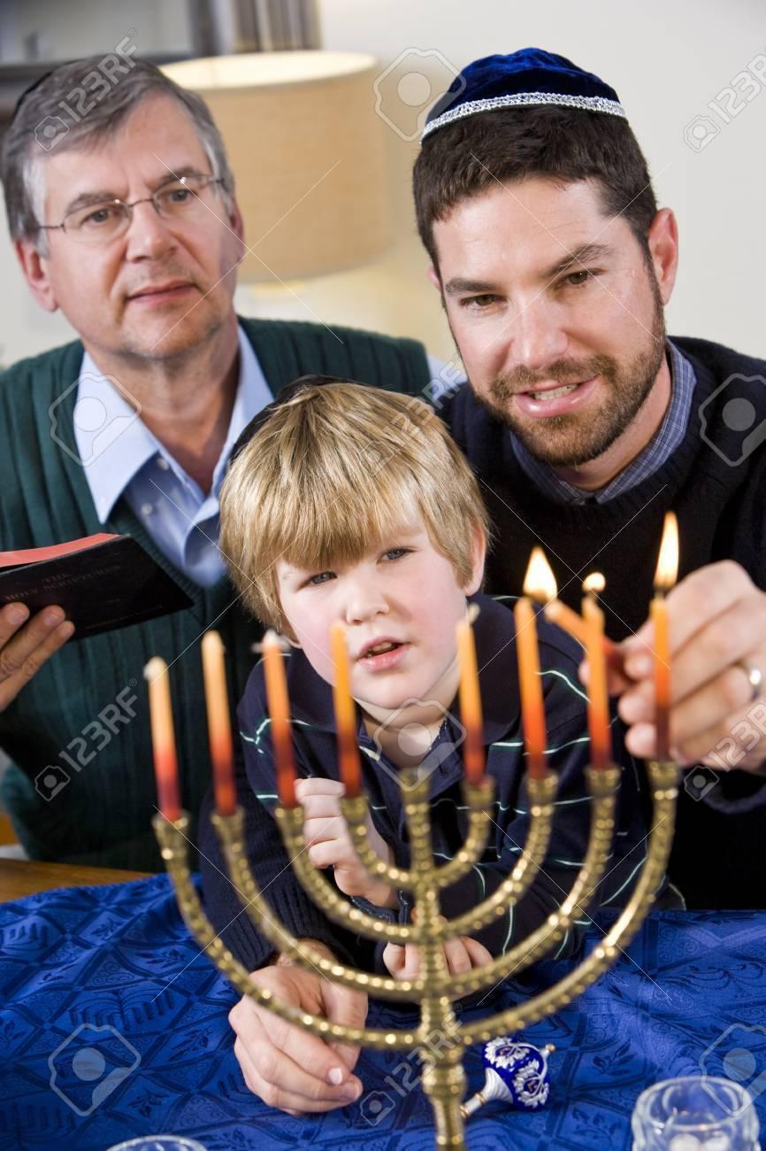 Three generation Jewish family lighting Chanukah menorah Stock Photo - 7635081