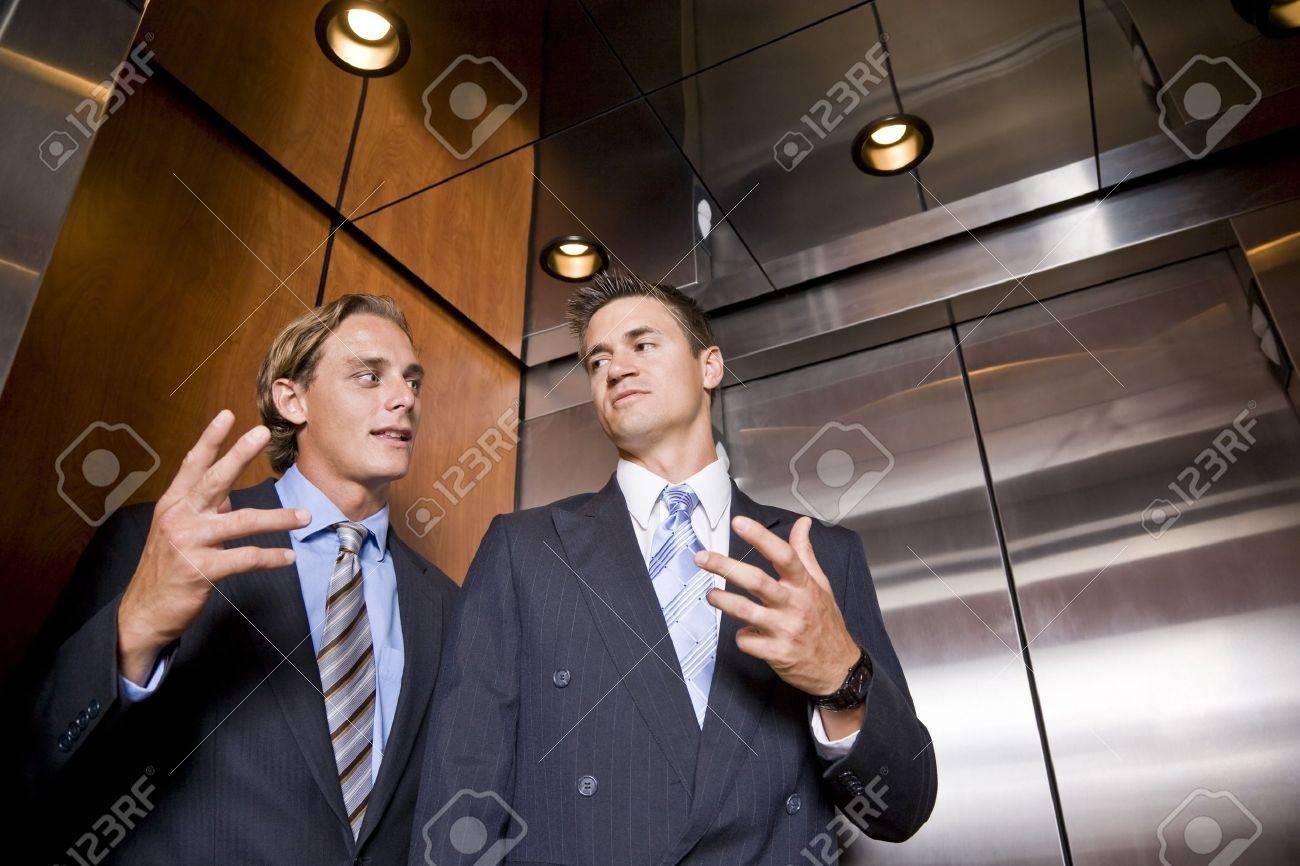 businessmen riding in elevator conversing stock photo picture and businessmen riding in elevator conversing stock photo 7698885