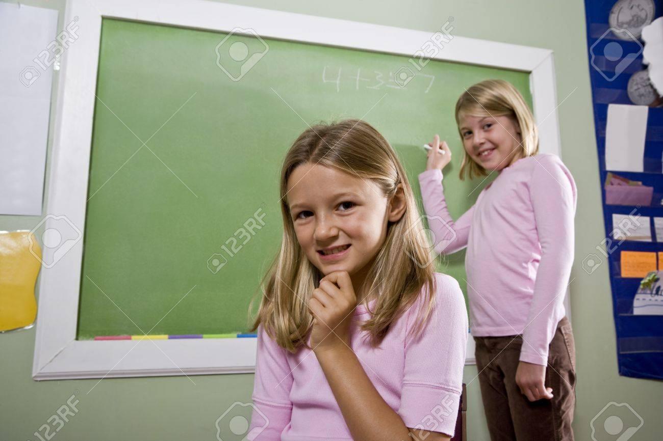 lassroom girls Back to school - 8 year old girls writing on blackboard in classroom, focus  on