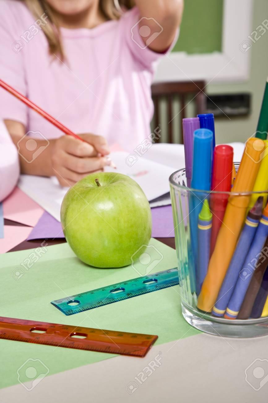 Apple for the teacher on student desk in classroom Stock Photo - 7826646