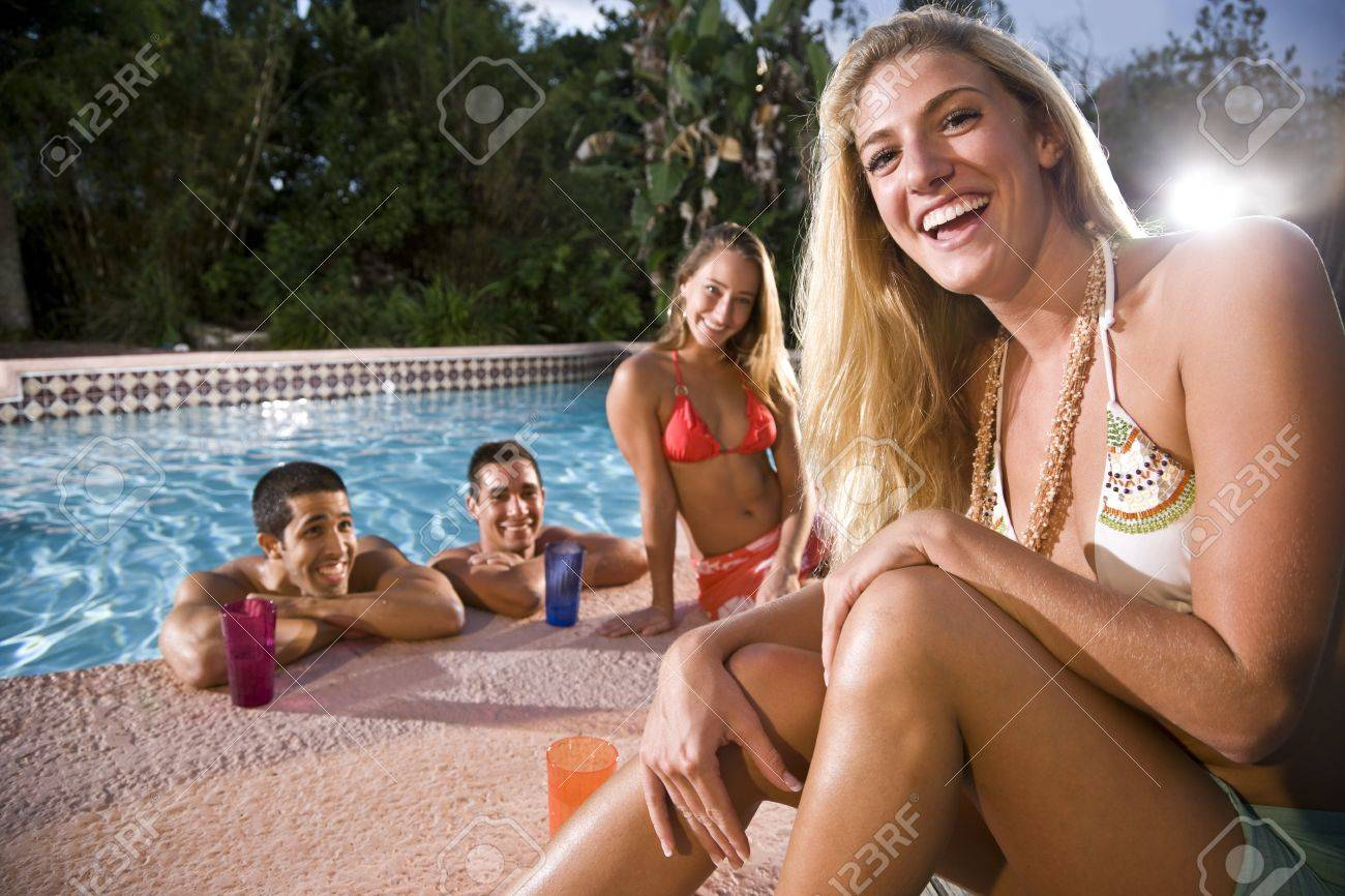 Young adults relaxing at swimming pool, focus on blond woman in foreground Stock Photo - 8063997