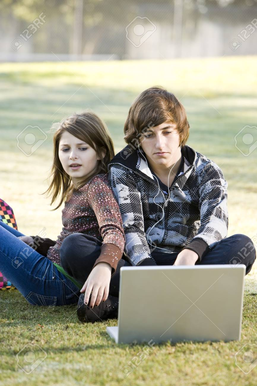 Boy and girl sitting on grass with laptop, online in park Stock Photo - 8167703