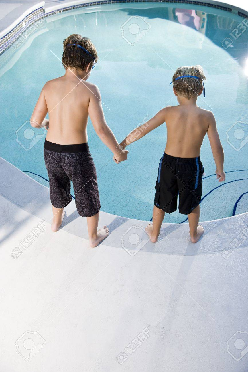 Boys, 7 and 9, looking down at water in swimming pool Stock Photo - 8167801