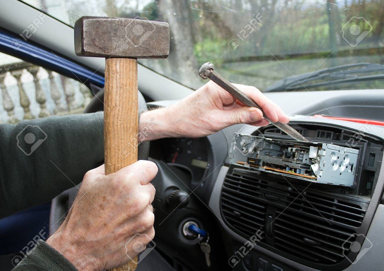 Hammer and chisel Amateur replaces car radio Stock Photo - 27662367