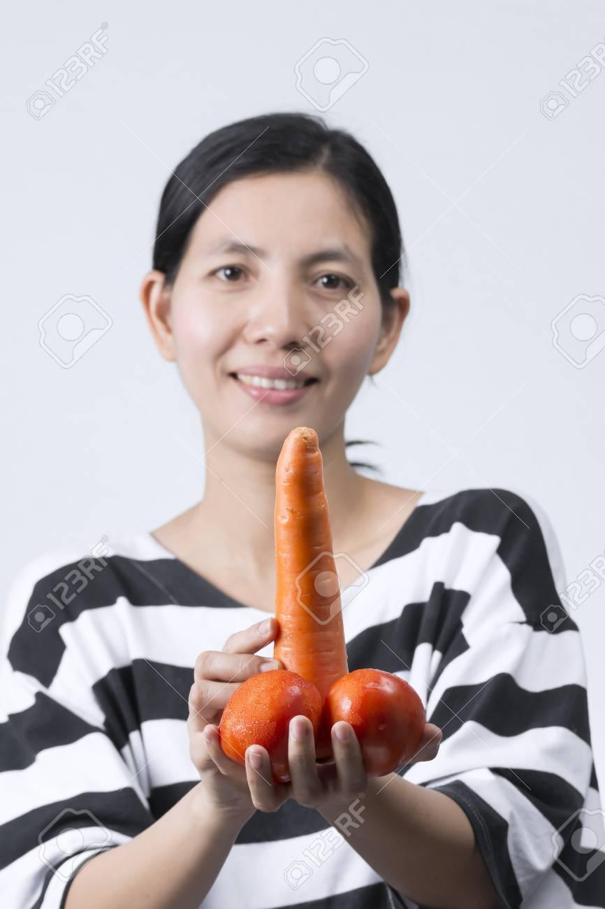 Mujer Tailandesa Asiática Que Sostiene La Zanahoria Y Los Tomates Rojos En Concepto Del Pene. Fotos, Retratos, Imágenes Y Fotografía De Archivo Libres De Derecho. Image 93792628.