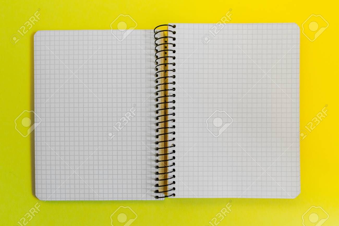 blank paper spiral notebook on yellow background stock photo