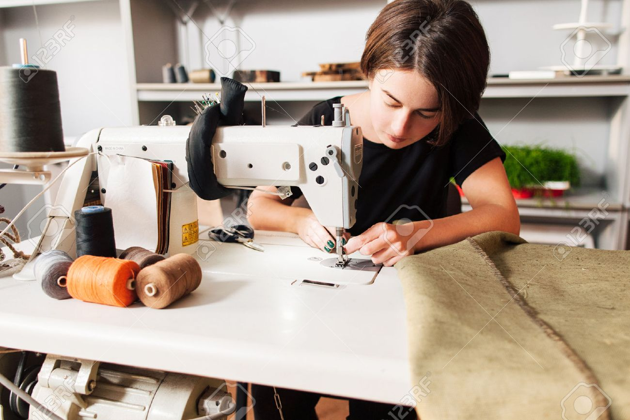 seamstress sews clothes and put thread in needle. Workplace of tailor - sewing machine, rolls of of thread, fabric, scissors. - 52171704