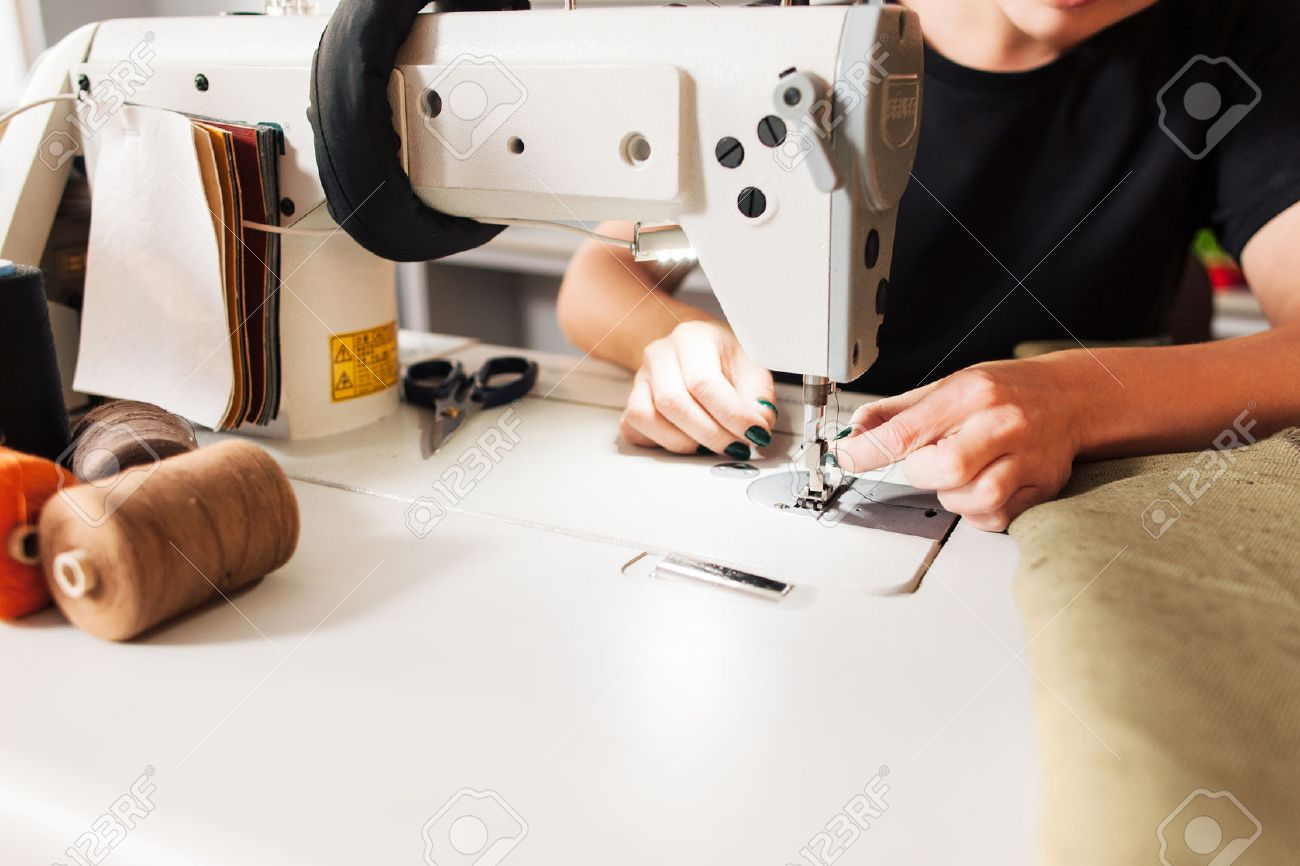 seamstress sews clothes and put thread in needle. Workplace of tailor - sewing machine, rolls of of thread, fabric, scissors. - 52171906